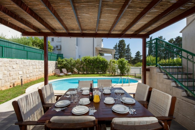 Covered outside dining table with a view on the private pool
